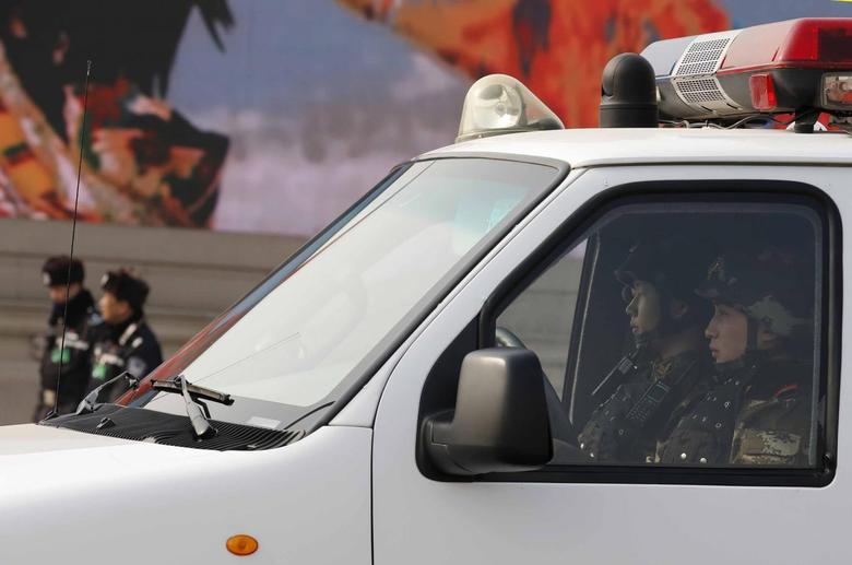 Paramilitary policemen (R) keep watch from a van as police officers (back L) stand guard at Tiananmen Square near the Great Hall of the People during a plenary session of the National People's Congress (NPC), in Beijing, March 9, 2014. REUTERS/Kim Kyung-Hoon