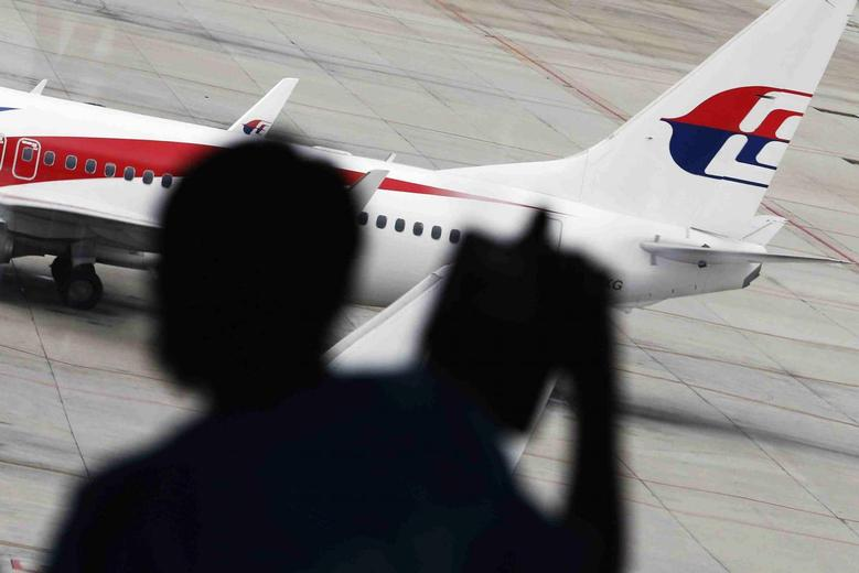A passenger takes pictures of a Malaysia Airlines plane at the Kuala Lumpur International Airport March 16, 2014. REUTERS/Damir Sagolj