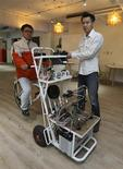 Kamm Kai-yu (R), a co-founder of boutique design studio Fabraft, displays a bicycle with a 3D printer installed in front, in Taipei March 13, 2014. REUTERS/Patrick Lin