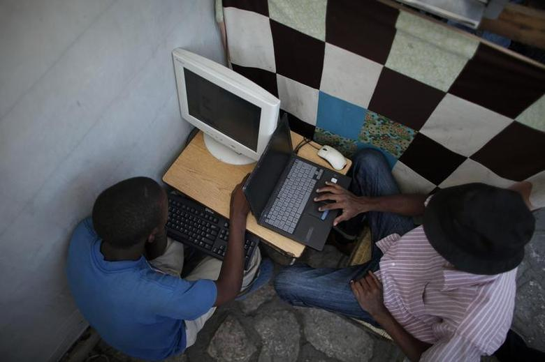 A resident reads emails at a makeshift internet cafe in front of the presidential palace in Port-au-Prince, Haiti January 30, 2010. REUTERS/Carlos Barria