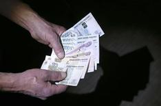 Российские рубли в руках у человека в Москве 7 марта 2014 года. Рубль дешевеет утром вторника после существенного восстановления накануне в ответ на спокойное проведение референдума в Крыму и мягкие санкции Запада против России. REUTERS/Sergei Karpukhin