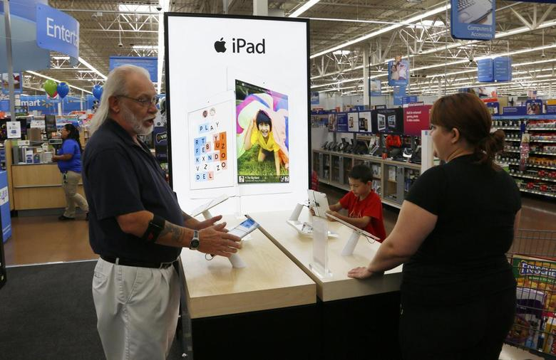 A Walmart employee (L) explains Apple iPad options to a customer at a Walmart Supercenter in Rogers, Arkansas June 6, 2013. REUTERS/Rick Wilking