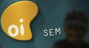 El logo de la compañía brasileña de telecomunicaciones Grupo Oi en una tienda en Sao Paulo, Brasil, oct 2 2013. La compañía brasileña de telecomunicaciones Grupo Oi SA logró compromisos de 14 bancos que accedieron a comprar hasta 6.000 millones de reales (2.500 millones de dólares) en una próxima oferta de acciones, dijo a Reuters el martes una fuente con conocimiento directo de la situación. REUTERS/Nacho Doce
