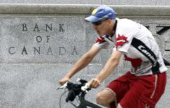 A cyclist rides past the Bank of Canada building in Ottawa July 17, 2012. REUTERS/Chris Wattie
