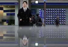 Pedestrians pass by an electronic board displaying stock prices, which are reflected in a polished stone surface, in Tokyo March 7, 2014. REUTERS/Yuya Shino