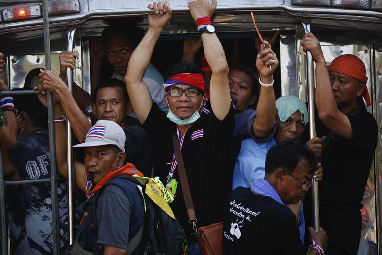 Anti-government protesters travel on a pick-up truck near the Interior Ministry building, which is being surrounded by fellow protesters, in Bangkok February 5, 2014. REUTERS/Damir Sagolj