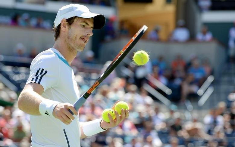 Andy Murray (GBR) selects tennis balls as he prepares to serve during his match against Milos Raonic (not pictured) during the BNP Paribas Open at the Indian Wells Tennis Garden. Raonic won 4-6, 7-5, 6-3. Mandatory Credit: Jayne Kamin-Oncea-USA TODAY Sports
