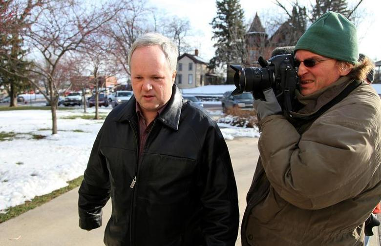William Melchert-Dinkel (L) is photographed by a news cameraman as he walks to the Rice County Courthouse to enter a not guilty plea in a case accusing him of aiding suicide in the deaths of an English man and Canadian woman in Faribault, Minnesota, November 19, 2010. REUTERS/Eric Miller
