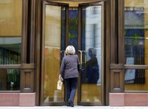 A woman enters the offices of private equity firm APAX in London May 18, 2012. REUTERS/Chris Helgren