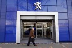 A man walks in front of a Peugeot automobile dealership in Paris December 13, 2013. REUTERS/Charles Platiau