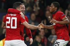 Manchester United's Robin van Persie (L) celebrates with Wayne Rooney and Antonio Valencia (R) a second goal against Olympiakos during their Champions League soccer match at Old Trafford in Manchester, northern England, March 19, 2014. REUTERS/Phil Noble