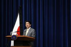 Japan's Prime Minister Shinzo Abe speaks next to the Japanese national flag, attached with a black ribbon to mourn victims during a news conference at his official residence in Tokyo March 10, 2014, a day before the third anniversary of the March 11, 2011 earthquake, tsunami and nuclear crisis that struck the nation's northeast. REUTERS/Issei Kato