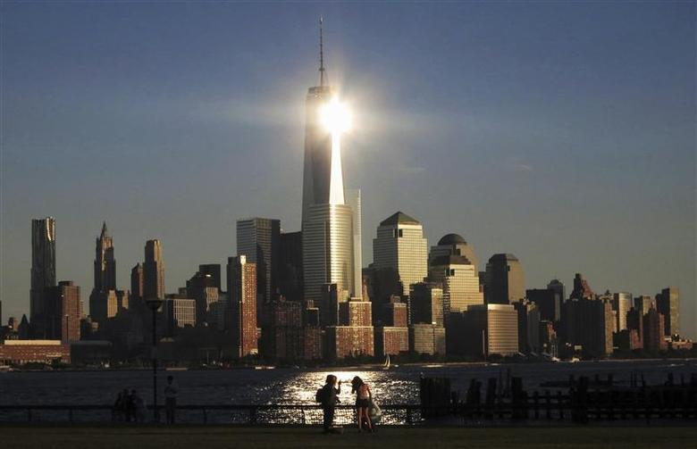 The sun reflects off New York's One World Trade Center as people stand in a park in Hoboken, New Jersey in this file photo from September 29, 2013. REUTERS/Gary Hershorn/Files