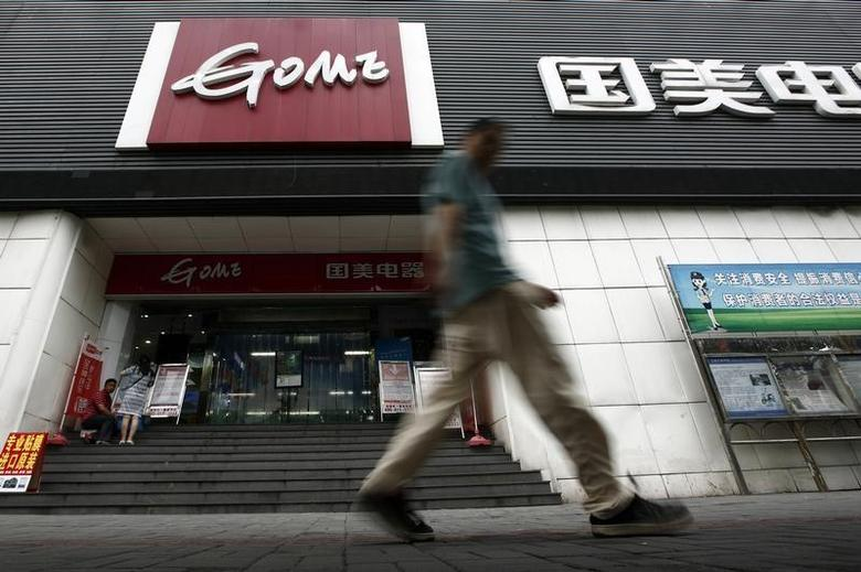 A man walks past a GOME store in Shanghai August 26, 2013. REUTERS/Aly Song