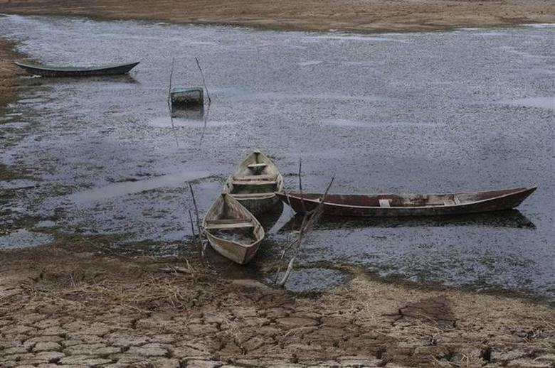 Boats lie on the dry lakebed of the Cocorobo Dam, down to 20 percent capacity, in the town of Canudos, in the part of Bahia State declared to be in a drought emergency, January 15, 2013. REUTERS/Lunae Parracho/Files