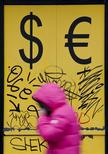 Пешеход проходит мимо пункта обмена валюты в Москве 3 марта 2014 года. Рубль лишь в небольшом минусе утром пятницы после ухудшения прогнозов суверенного рейтинга РФ агентствами Fitch и S&P, поскольку предстоящие на следующей неделе крупные и важные для экспортеров налоги сдерживают его ослабление. REUTERS/Maxim Shemetov