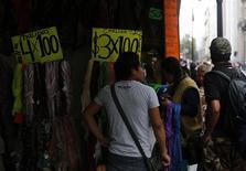 Una mujer revisa unas prendas de vestir en una tienda en Ciudad de México, oct 26 2013. Las ventas al menudeo de México bajaron un 0.3 por ciento en enero contra el mes previo, dijo el viernes el instituto de estadísticas. REUTERS/Tomas Bravo