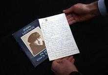 A manuscript written by John Lennon entitled 'Henry and Harry' is held for the cameras by a Sotheby's employee, London March 21, 2014. REUTERS/Paul Hackett