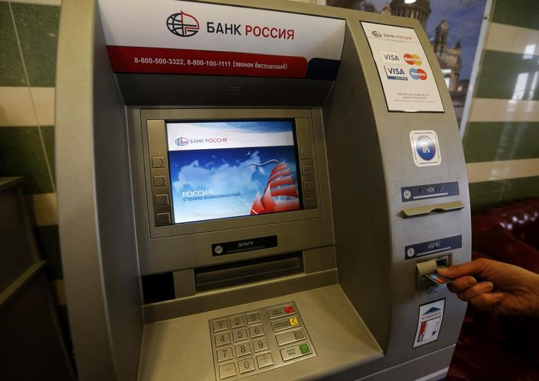 A client uses a Bank Rossiya automated teller machine (ATM) in St. Petersburg March 21, 2014. REUTERS/Alexander Demianchuk