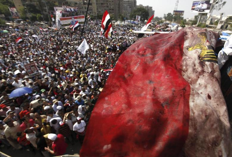 An Egyptian flag stained with blood flutters over members of the Muslim Brotherhood and supporters of deposed Egyptian President Mohamed Mursi as they shout slogans during a protest outside Raba El-Adwyia mosque in Cairo July 8, 2013, following clashes in front of the Republican Guard headquarters. REUTERS/Mohamed Abd El Ghany