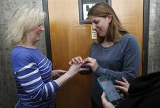 Two women exchange rings during their wedding ceremony in the hallway of the Oakland County Courthouse as the woman officiating the wedding reads the marriage vows from her cell phone, after a Michigan federal judge ruled a ban on same-sex marriage violates the U.S. Constitution and must be overturned in Pontiac, Michigan March 22, 2014. REUTERS/Rebecca Cook
