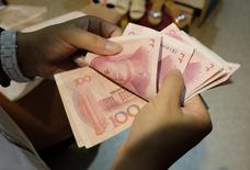 A woman counts Chinese yuan notes at a market in Beijing, July 1, 2013. REUTERS/Jason Lee