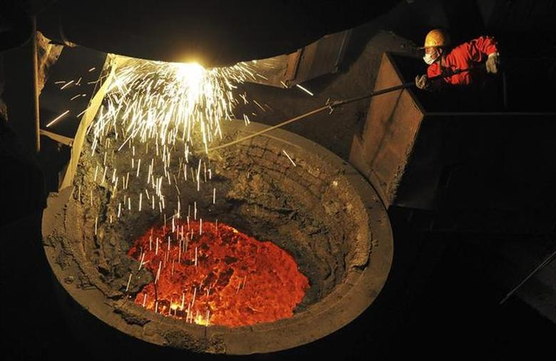 An employee works above a furnace containing molten steel at a factory of Dongbei Special Steel Group Co. Ltd. in Dalian, Liaoning province January 30, 2014. REUTERS/China Daily/Files