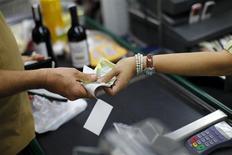 Un cliente paga con bolívares al interior de un supermercado en Caracas, feb 8 2013. Venezuela comenzó a operar el lunes un nuevo mecanismo de cambio basado en la oferta y la demanda, dijo un funcionario con conocimiento del tema, en un intento por abatir el dólar en el mercado negro e inyectar más divisas en la nación afectada por una severa escasez de productos básicos. REUTERS/Jorge Silva