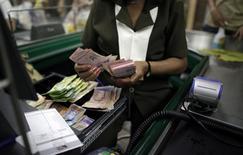 Una cajera cuenta bolívares en la caja de un supermercado en Caracas, ene 12 2010. El tipo de cambio promedio del nuevo sistema de divisas que estrenó el lunes Venezuela fue de 50-55 bolívares por dólar, unas ocho veces el precio del cambio preferente oficial, informaron operadores. REUTERS/Jorge Silva