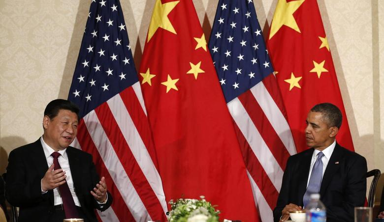 China's President Xi Jinping speaks during his meeting with U.S. President Barack Obama (R), on the sidelines of a nuclear security summit, in The Hague March 24 2014. REUTERS/Kevin Lamarque