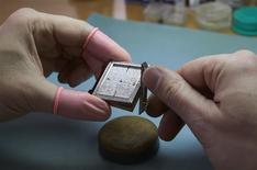 A watchmaker adjusts the components of the Autore 2TA watch model at Buccellati workshop in Chiasso March 14, 2014. REUTERS/Denis Balibouse