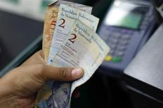 Un cajero cuenta bolívares en un supermercado de Caracas, feb 8 2013. Los bonos venezolanos subían el martes en una reacción positiva del mercado tras la puesta en marcha de un sistema cambiario de libre flotación, que en la víspera ofreció dólares ocho veces por encima del precio oficial en su sesión de apertura. REUTERS/Jorge Silva