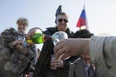 Мужчина наливает шампанское в стакан во время трансляции выступления президента РФ Владимира Путина в Севастополе 18 марта 2014 года. Крымская кампания Владимира Путина отвлекла население от повседневных экономических проблем, но эффект не будет долгосрочным, а дальнейшая внутриполитическая стабильность зависит от способности властей России вернуть стагнирующую экономику к росту и избежать внешнеэкономического шока от кризиса на Украине и противостояния с Западом, считает научный руководитель Центра стратегических разработок Михаил Дмитриев. REUTERS/Baz Ratner