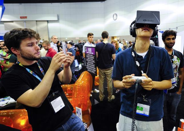 Software designer Julian Kantor (L), who created ''The Recital'' takes a picture of Jonathan Feng (R) as he uses the Oculus Rift virtual reality headset to experience his program during E3 in Los Angeles, California June 12, 2013. REUTERS/Gus Ruelas