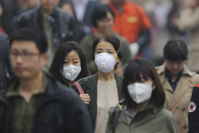 People wearing masks walk along a street on a heavy hazy day in Beijing, March 27, 2014. REUTERS/Jason Lee