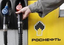 Человек держит в руках заправочный шланг на автозаправке Роснефти в Санкт-Петербурге 23 октября 2012 года. РФ может потерять почти пятую часть нефтепереработки после запланированного на 2015 год увеличения экспортной пошлины на мазут до уровня нефтяной, что пополнит казну, но грозит дефицитом моторного топлива в стране, прогнозируют аналитики. REUTERS/Alexander Demianchuk