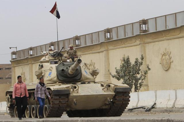 People walk past an Egyptian army tank positioned outside Cairo's Tora prison, March 23, 2014. REUTERS/Mohamed Abd El Ghany