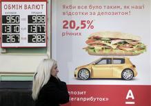 Près d'un bureau de change à Kiev, le mois dernier. Le FMI va débloquer une aide de 14 milliards à 18 milliards de dollars (10,2 à 13 milliards d'euros) pour l'Ukraine, initiative qui permettra de débloquer de nouveaux crédits d'un montant total de 27 milliards de dollars sur les deux prochaines années. /Photo prise le 26 février 2014/REUTERS/Konstantin Chernichkin