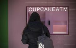 """A woman makes a purchase from the Cupcake """"ATM"""" at Sprinkles Cupcake Bakery in New York City's Upper East Side in Manhattan, March 26, 2014. REUTERS/Mike Segar"""