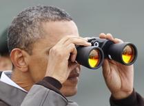Президент США Барак Обама смотрит в бинокль в сторону Северной Кореи в демилитаризованной зоне к северу от Сеула 25 марта 2012 года. США не видят признаков того, что российские силы вдоль границы с Украиной проводят какие-либо весенние учения, которыми объясняла Москва концентрацию войск в регионе, заявил Пентагон. REUTERS/Yuriko Nakao