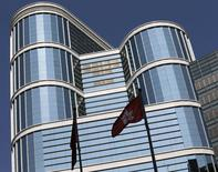 A Hong Kong flag (R) flutters outside CITIC Tower, the corporate headquarters of CITIC Pacific Ltd in Hong Kong March 27, 2014. REUTERS/Bobby Yip