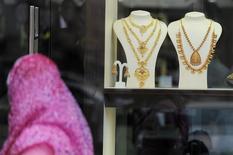 Женщина проходит мимо витрины ювелирного магазина в Абу-Даби 23 апреля 2013 года. Цены на золото растут, но остаются вблизи шестинедельного минимума и снизятся вторую неделю подряд из-за улучшения прогнозов для американской экономики. REUTERS/Ben Job