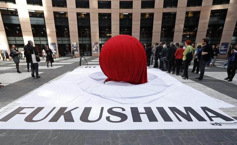 A banner that reads ''Fukushima'' is placed in front of a giant symbolic Japan's national flag to mark the third year anniversary of the March 11, 2011 earthquake and tsunami, at the European Parliament in Strasbourg, March 11, 2014. REUTERS/Vincent Kessler