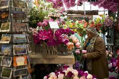Una mujer revisa unas flores en una tienda en Amsterdam, abr 26 2013. El optimismo en la economía de la zona euro mejoró más de lo esperado en marzo, cuando la confianza del consumidor europeo mostró el mayor incremento mensual en casi cinco años. REUTERS/Cris Toala Olivares