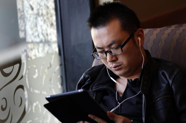 A man use his iPad inside a local coffee shop in downtown Shanghai November 28, 2013. REUTERS/Carlos Barria