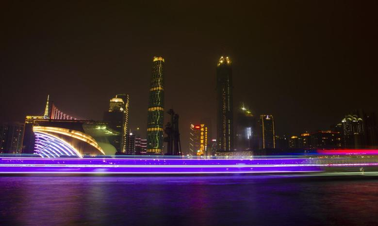 A long exposure picture of boats passing by a business area along the Pearl River in Guangzhou, Guangdong province, March 22, 2014. REUTERS/Alex Lee
