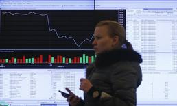 Женщина проходит мимо экрана с рыночными котировками и графиками на Московской бирже 14 марта 2014 года. Российские фондовые индексы начали торги понедельника чуть выше уровней пятничного закрытия, дополняя двухнедельное повышение. REUTERS/Maxim Shemetov