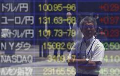Мужчина смотрит на табло, отображающее колебания курсов японской иены относительно других валют, в Токио 10 мая 2013 года. Курс иены снижается, так как спрос на нее как низкорискованный актив сократился из-за перспективы экономических стимулов в Китае. REUTERS/Issei Kato