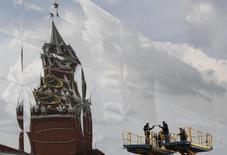 Спасская башня Кремля отражается в павильоне на Красной площади в Москве 8 июля 2013 года. Рабочая неделя в Москве сохранит тенденцию прошедших выходных - жителей столицы ждет минус по ночам и легкий плюс в светлое время суток, ожидают синоптики. REUTERS/Sergei Karpukhin