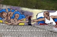 Граффити, изображающее президента России Владимира Путина и украинский народ, в Симферополе 28 марта 2014 года. Россия и Запад готовятся к затяжному противостоянию после аннексии Крыма, от которой у Москвы может разыграться аппетит к другим территориям бывшего СССР и не только. REUTERS/Shamil Zhumatov